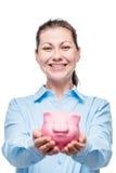La donna felice giudica un porcellino salvadanaio pieno di soldi, foto fotografia stock libera da diritti