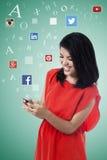 La donna felice gode della rete sociale sul cellulare Fotografia Stock