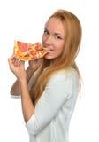 La donna felice gode di di mangiare la fetta di pizza di merguez con i pomodori Fotografie Stock