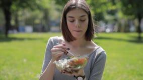 La donna felice gode di di mangiare l'insalata fresca che si siede al parco dell'estate stock footage
