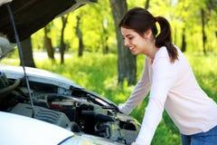 La donna felice guarda sotto l'automobile del cappuccio Immagini Stock Libere da Diritti