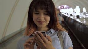 La donna felice guida la scala mobile giù al sottopassaggio facendo uso di uno smartphone stock footage