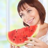 La donna felice mangia l'anguria Fotografie Stock