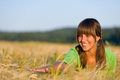 La donna felice nel campo di cereale di tramonto gode del sole Fotografia Stock Libera da Diritti