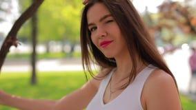 La donna felice nel parco della citt? gode di un giorno di estate, di un fronte di giro e di una strizzatina d'occhio stock footage