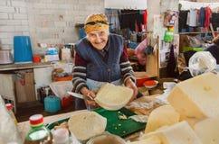 La donna felice più anziana vende il formaggio casalingo organico sul mercato georgiano del ` s dell'agricoltore del villaggio Immagine Stock Libera da Diritti