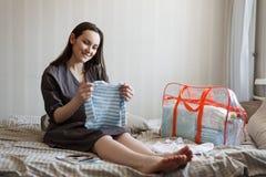La donna felice raccoglie le cose per i neonati in una borsa, tasse nell'ospedale immagine stock