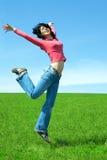 La donna felice salta nel campo Immagini Stock Libere da Diritti