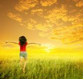 La donna felice salta nel campo e nel tramonto di erba Fotografia Stock