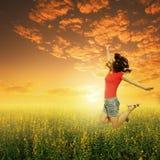 La donna felice salta nel campo e nel tramonto di erba Il suo Succes Immagini Stock Libere da Diritti