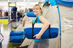 La donna felice sceglie il campo della tenda nei prodotti per il tempo libero del deposito Fotografia Stock