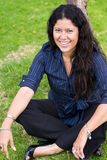 La donna felice si è seduta su erba Immagini Stock