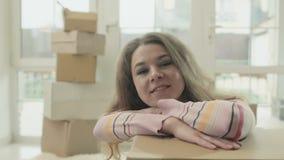 La donna felice si appoggia disimballa la scatola archivi video