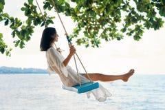 La donna felice spensierata su oscillazione sui bei paradiso tira immagini stock
