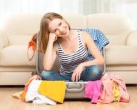 La donna felice sta imballando la valigia a casa Immagini Stock