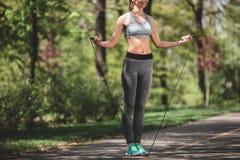 La donna felice sta preparandosi con la corda di salto fuori Fotografia Stock