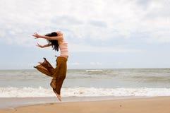 La donna felice sta saltando in spiaggia immagine stock libera da diritti