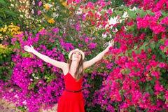 La donna felice sta stando fra i bei fiori variopinti Fotografia Stock