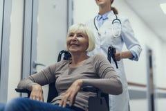 La donna felice sta viaggiando sul passeggino in clinica fotografie stock libere da diritti