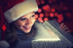 La donna felice in un cappuccio di Natale apre la scatola magica Fotografie Stock