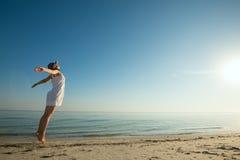 La donna felice in un vestito bianco salta sulla riunione del sole Fotografia Stock