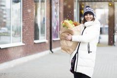 La donna felice va con il sacco di carta delle verdure e dell'alimento dalla drogheria Preparando per il Natale di celebrazioni d fotografie stock