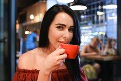 La donna femminile abbastanza giovane esamina la macchina fotografica, tiene la tazza disponibila e Fotografia Stock