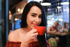 La donna femminile abbastanza giovane esamina la macchina fotografica, tiene la tazza disponibila e Immagini Stock Libere da Diritti
