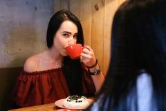 La donna femminile abbastanza giovane tiene la tazza disponibila e beve caffè AG Immagini Stock Libere da Diritti