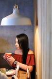 La donna femminile abbastanza giovane tiene la tazza disponibila e beve caffè AG Immagine Stock Libera da Diritti