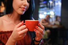 La donna femminile abbastanza giovane tiene la tazza disponibila e beve caffè AG Fotografia Stock