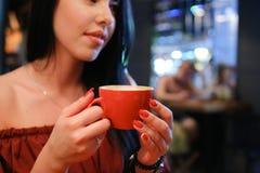 La donna femminile abbastanza giovane tiene la tazza disponibila e beve caffè AG Fotografia Stock Libera da Diritti