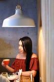 La donna femminile abbastanza giovane tiene la tazza disponibila e beve caffè AG Immagini Stock