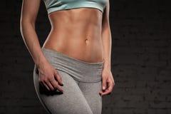 La donna femminile di forma fisica con l'ente muscolare, fa il suo allenamento, ABS Fotografia Stock
