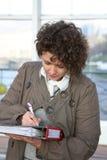 La donna firma i documenti fotografia stock