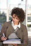 La donna firma i documenti immagini stock