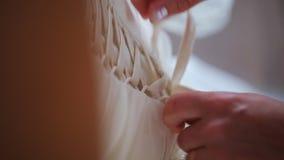 La donna fissa esattamente l'allacciamento di seta sul garnment del fondamento della fidanzata stock footage