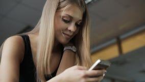 La donna fissa in telefono e nel sorridere durante una pausa fra l'allenamento archivi video