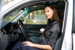 La donna fissa una cintura di sicurezza nell'automobile Fotografia Stock