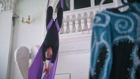 La donna flessibile esegue una cordicella nell'aria che appende sulla seta aerea stock footage