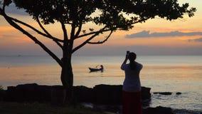 La donna fotografa un declino con la barca sullo smartphone Barca sull'orizzonte di tramonto del mare aperto stock footage