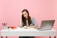 La donna frustrata nella disperazione che pende a disposizione lo sguardo giù si siede, lavoro allo scrittorio bianco con il comp fotografia stock