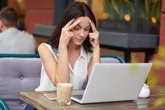 La donna frustrata stressante ha emicrania, ritiene stanca del lavoro distante, tiene le mani sulle tempie, prove per concentrars immagine stock libera da diritti