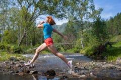 La donna funziona giù un fiume della montagna immagini stock libere da diritti
