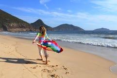 La donna funziona lungo la spiaggia con una bandiera australiana Immagini Stock Libere da Diritti