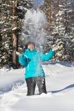 La donna getta sulla neve nella foresta dell'inverno Fotografie Stock Libere da Diritti
