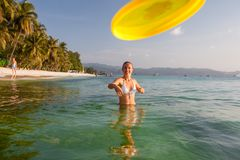 La donna gioca il frisbee nell'acqua di bello oceano Fotografia Stock Libera da Diritti