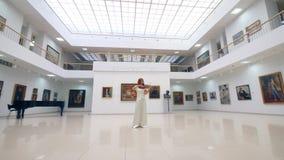 La donna gioca il violino di legno in una grande stanza in museo stock footage