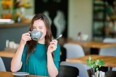 La donna gode del caffè saporito che mangia la prima colazione al caffè all'aperto Caffè bevente della giovane donna urbana felic Immagini Stock Libere da Diritti