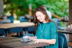 La donna gode del caffè saporito che mangia la prima colazione al caffè all'aperto Caffè bevente della giovane donna urbana felic Immagini Stock